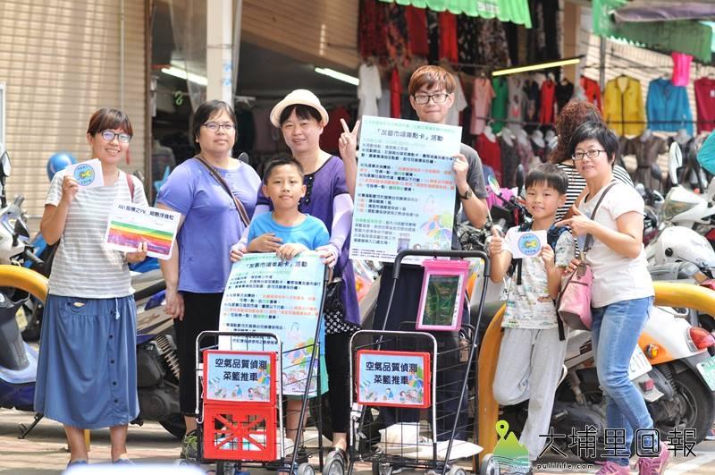 志工推著空氣品質偵測菜籃推車,在埔里第三市場推廣「友善市場集點卡」活動。(柏原祥 攝)