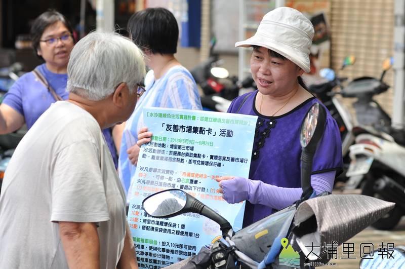 志工拿著看板,向第三市場買菜民眾推廣「友善市場集點卡」活動。(柏原祥 攝)