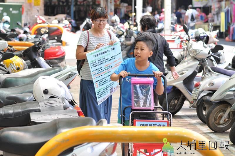 志工推著空氣品質偵測菜籃推車,向第三市場民眾推廣「友善市場集點卡」活動。(柏原祥 攝)