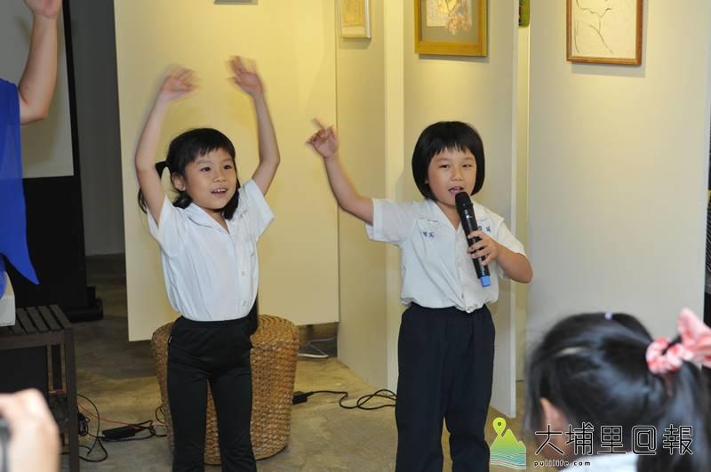 在費爾《童心未泯》畫展中,育英國小三位小朋友獻唱可愛的數星星歌曲,「希望星星有聽見,請它告訴你, 我愛你~」。(柏原祥 攝)