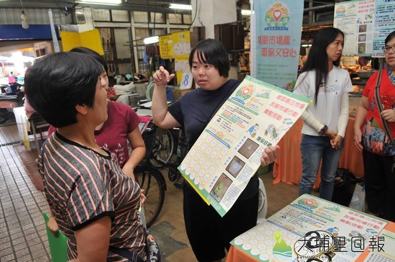 埔里鎮第三市場推動友善環境計畫,志工說明友善行動集點換取禮物辦法。(柏原祥 攝)