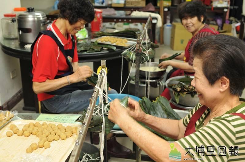 陳綢阿嬤帶領良顯堂的志工料理素粽,大伙帶著歡喜心包粽。(柏原祥 攝)
