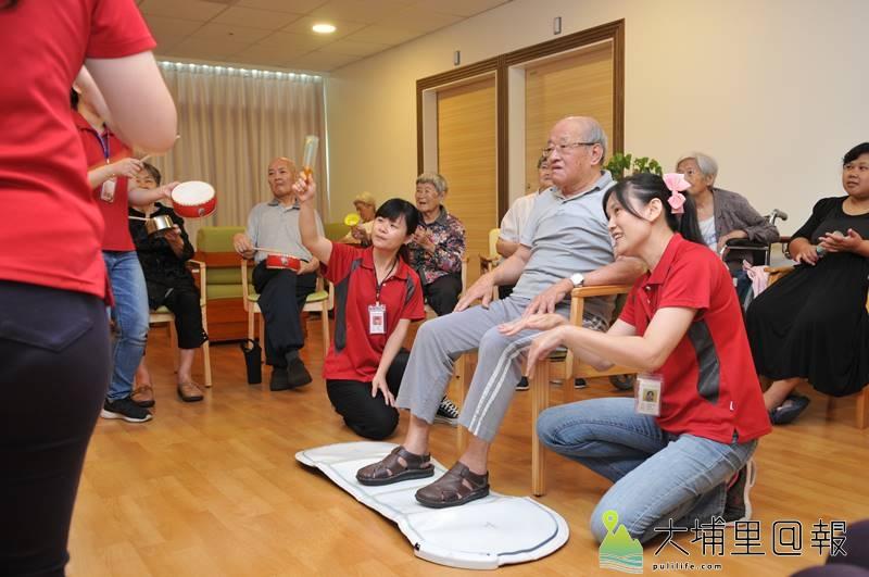 南投縣失智共同照護中心在埔基醫院長照教學大樓成立揭牌,圖為老人在護理人員引導下,透過電玩活動筋骨,訓練反應。(柏原祥 攝)