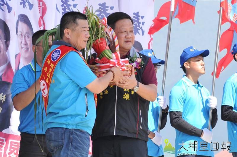 埔里鎮長候選人吳國昌競選總部成立,同黨的埔里鎮長周義雄送上蒜苗祝他「高票凍蒜」。