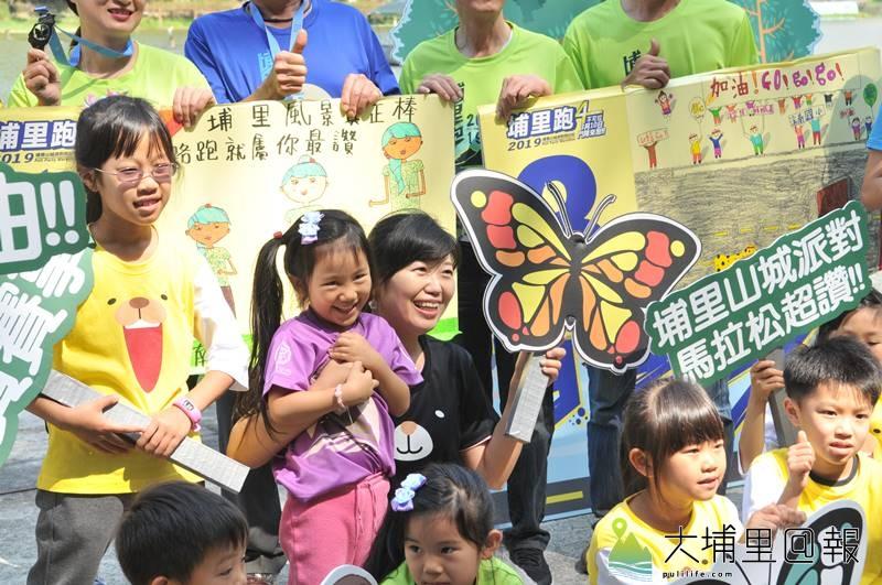 2019山城派對馬拉松即將開跑,小朋友手拿蝴蝶意象的告示牌歡迎跑者來埔里遊玩。(柏原祥 攝)