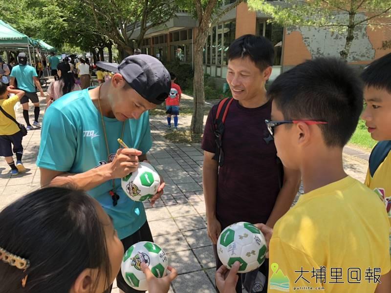 台電足球Fun電營首次在埔里鎮宏仁國中舉辦,活動結束後,學童拿著小足球請球星簽名。(柏原祥 攝)